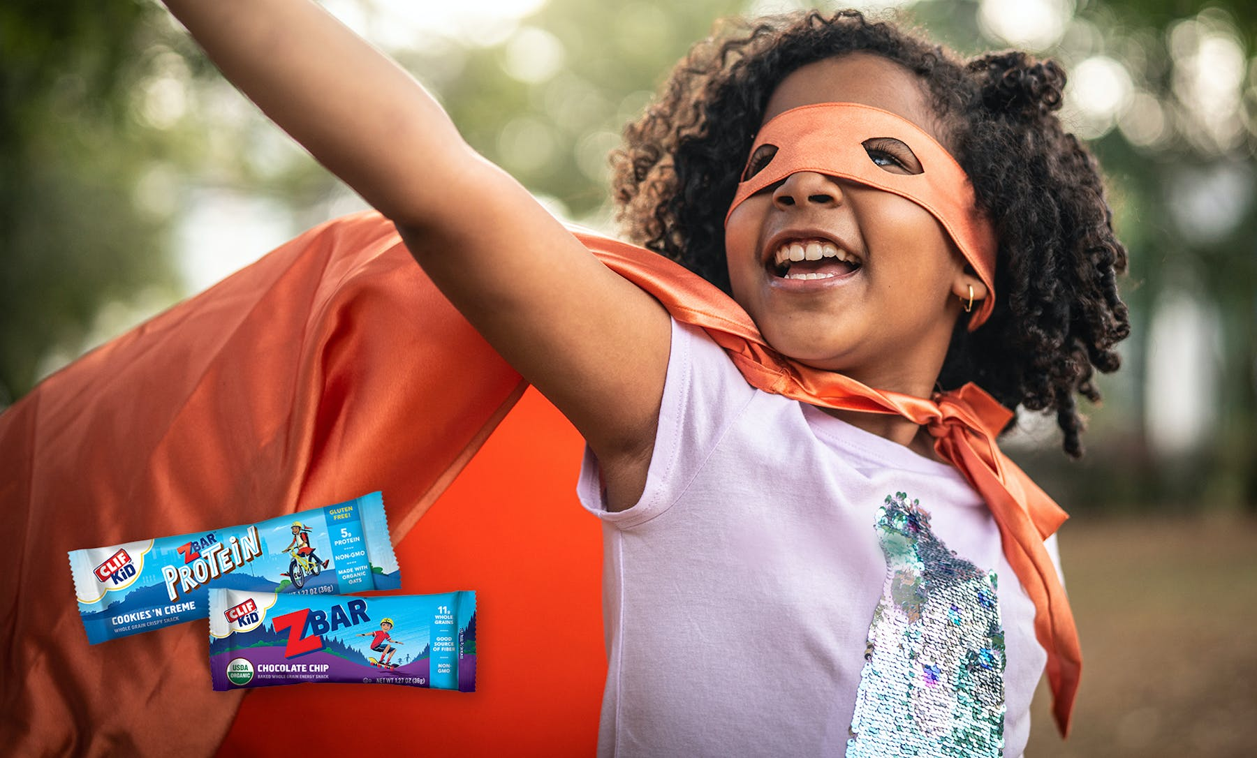 Girl in mask and cape with CLIF Kid bars