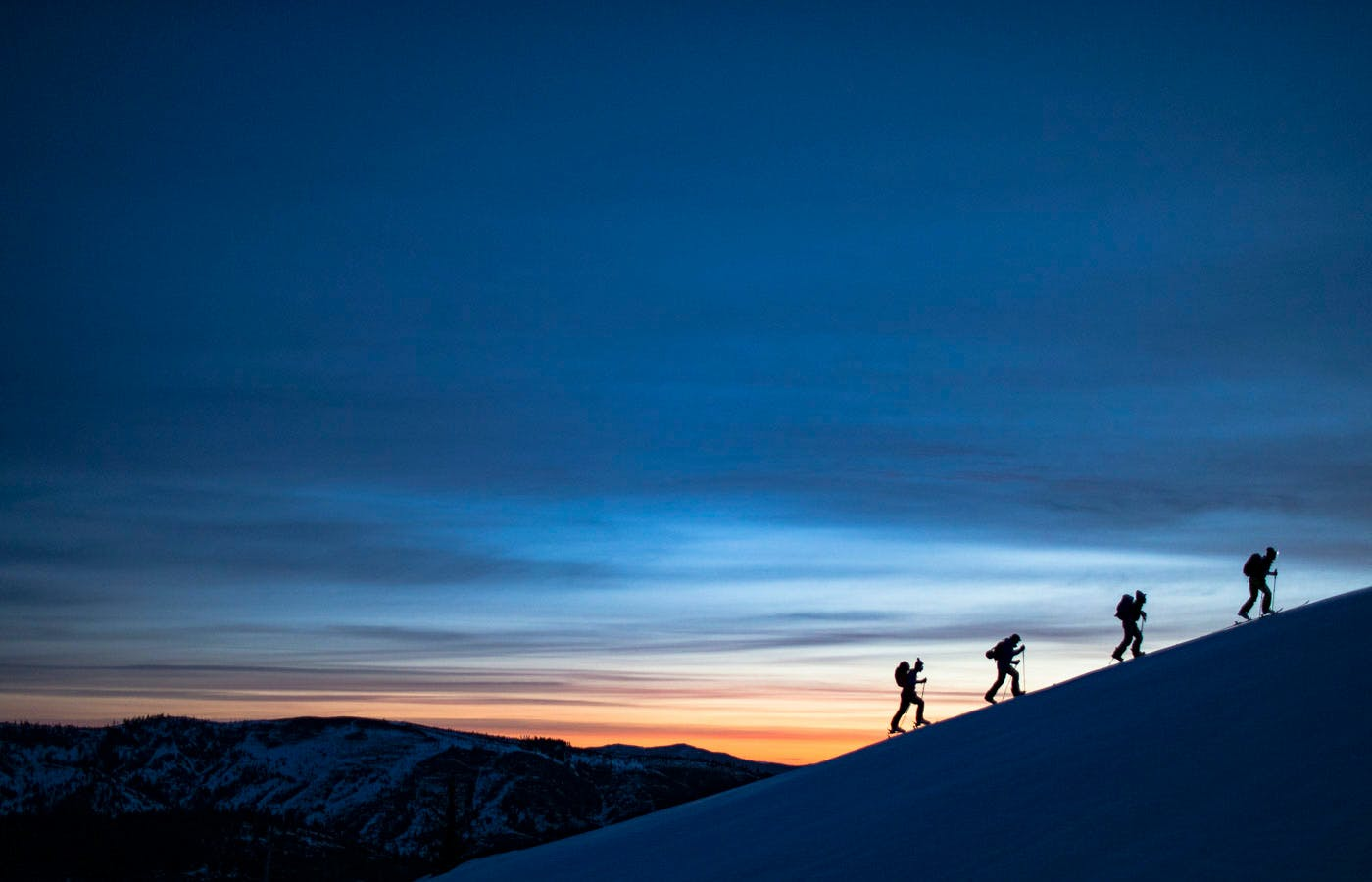 Hikers hiking up mountain at sunset