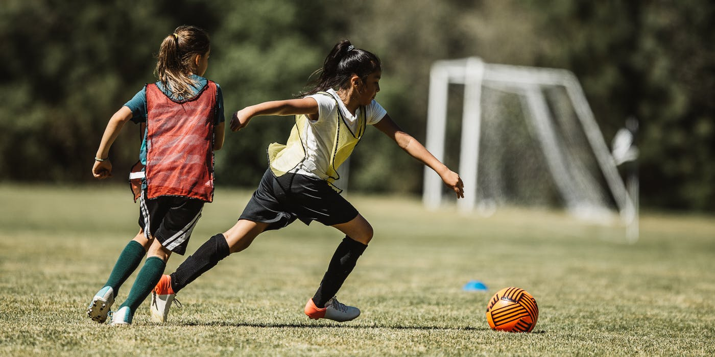 Two girls playing soccer on field