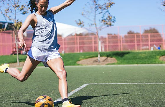 Christen Press kicking soccer ball