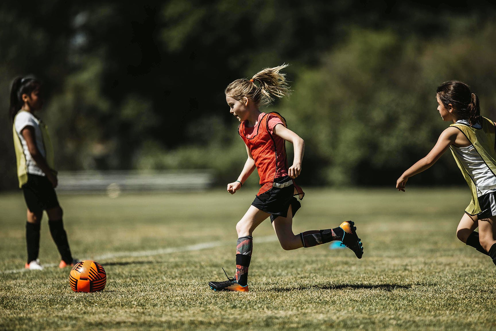 Girl in red jersey playing soccer