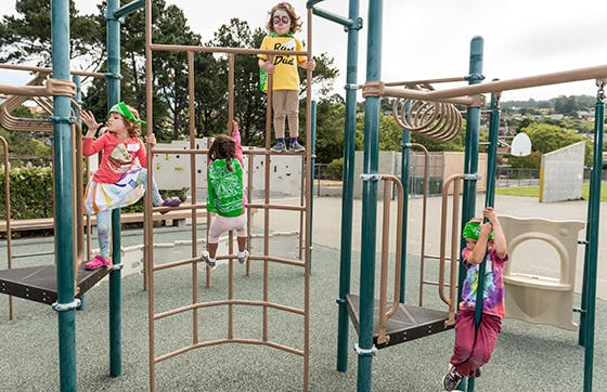 Rainbow Day Camp kids climbing on play structure