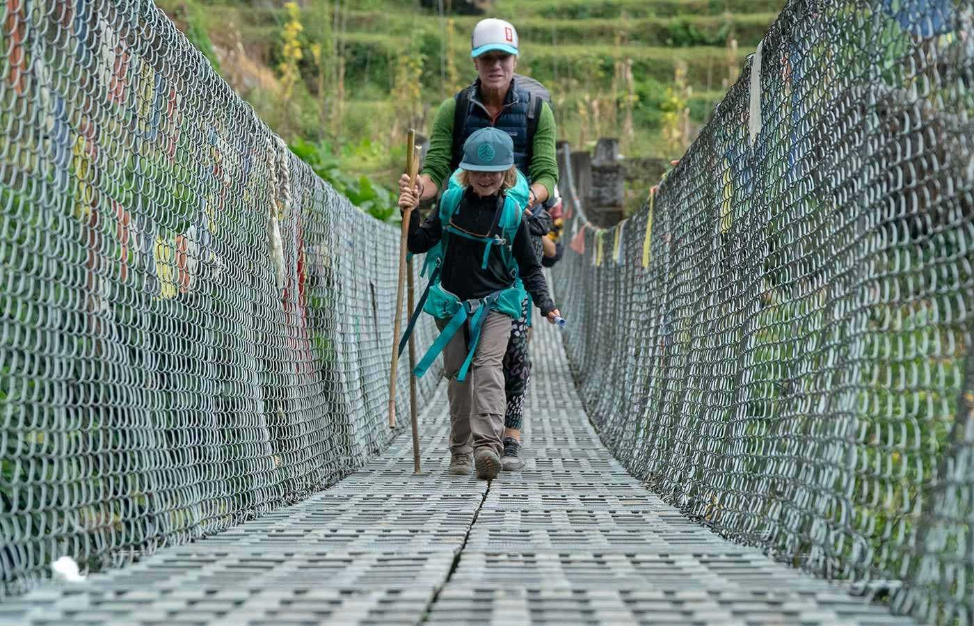 Mom and son crossing bridge in Nepal