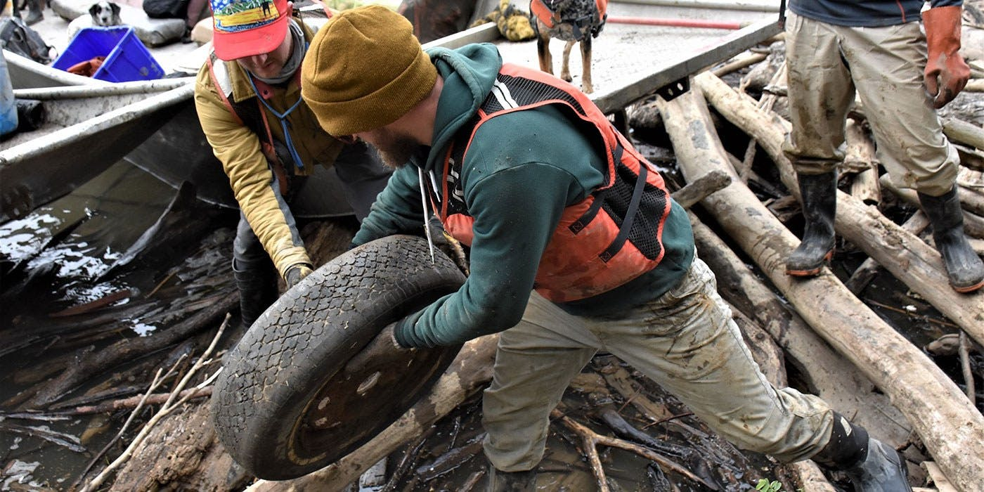 Clif Bar employee Eric Walle lifts tire out of Ohio River