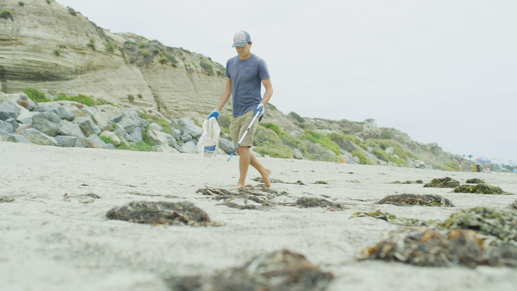 World Cleanup Day volunteer picking up trash on the beach